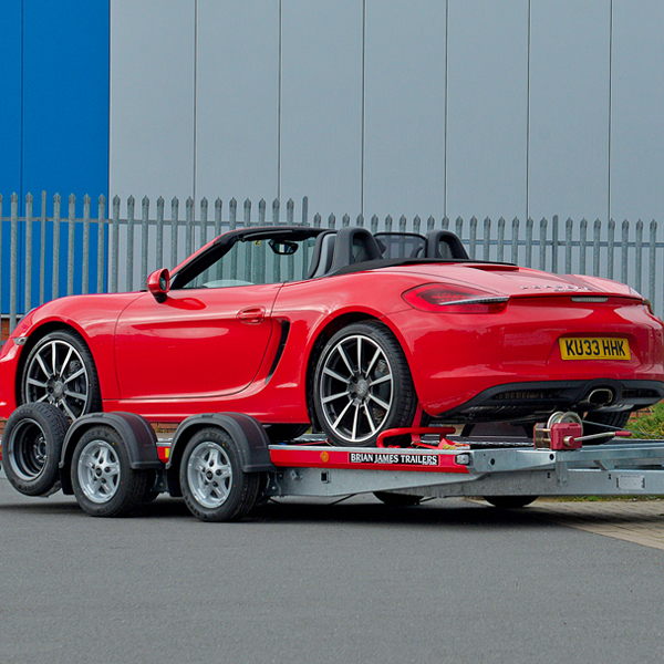 a Brian James Trailer transporting a red sports car
